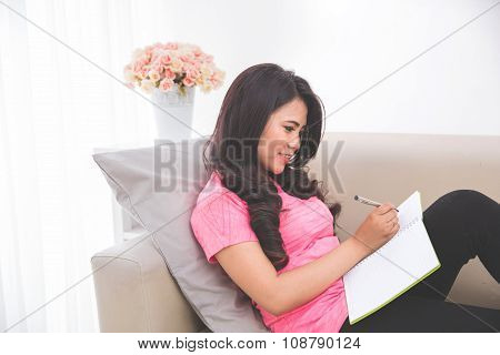 Woman Reading Notebook Sitting On A Couch