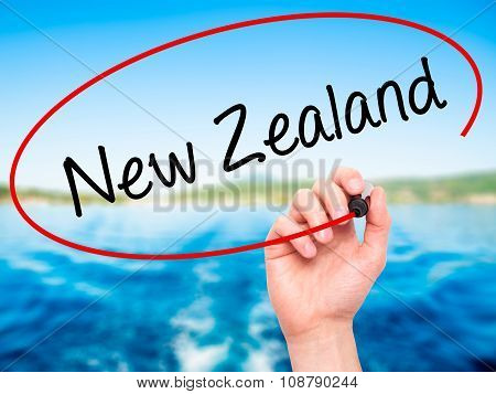 Man Hand writing New Zealand with black marker on visual screen.