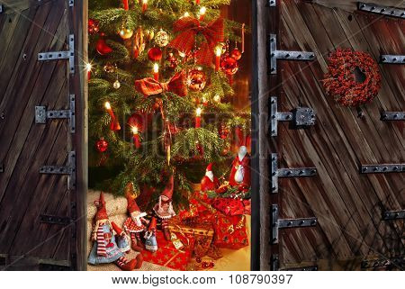 Great door opening into a room with decorated christmas tree and gift on christmas evening