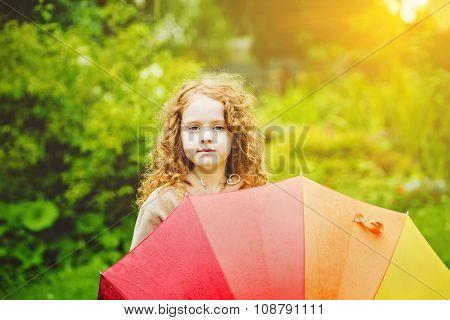 Little girl with rainbow umbrella under sunshine.