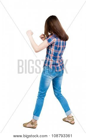 skinny woman funny fights waving his arms and legs. Isolated over white background. A young girl in a checkered blue with red stripes stands in boxing pose.
