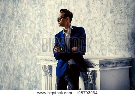 Vogue shot of a handsome elegant man in a suit posing in vintage interior. Men's beauty, fashion.