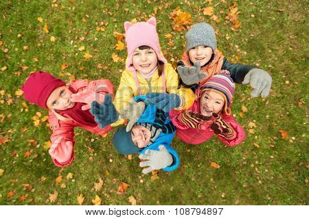 childhood, leisure, friendship and people concept - group of happy children waving hands in autumn park from top