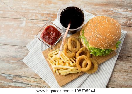 fast food and unhealthy eating concept - close up of hamburger or cheeseburger, deep-fried squid rings, french fries, cola drink and ketchup on wooden table