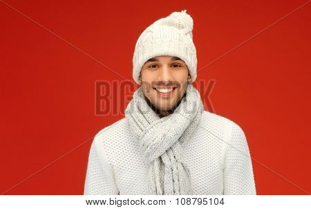 people, christmas, fashion, season and clothing concept - handsome man in winter wear over red background