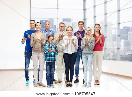 family, gender, generation and people concept - group of smiling men, women and boy applauding over empty office room or home