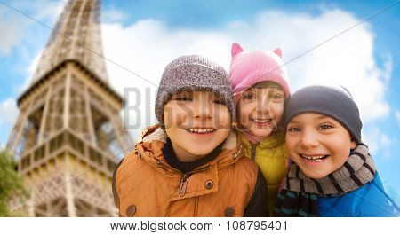 childhood, tourism, travel, vacation and people concept - group of happy kids over eiffel tower and sky background