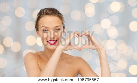 beauty, people, love, valentines day and make up concept - smiling young woman with pink lipstick on lips showing heart shape hand sign over holidays lights background