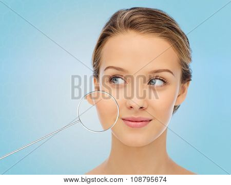 beauty, people and health concept - smiling young woman face over blue background with magnifier showing perfect skin