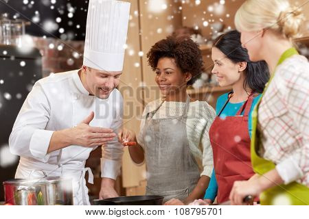 cooking class, culinary, food and people concept - happy group of women and male chef cook cooking in kitchen over snow effect