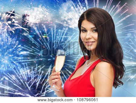 people, holidays, christmas, new year party and celebration concept - beautiful sexy woman in red dress with champagne glass over night city and firework background