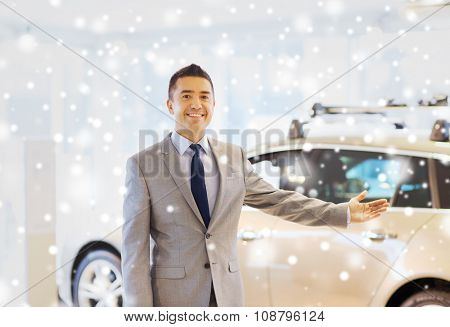 auto business, car sale, consumerism and people concept - happy man at auto show or salon over snow effect