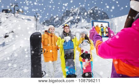winter sport, technology, leisure, friendship and people concept - happy friends with snowboards and tablet pc computer taking picture over snow and mountain background