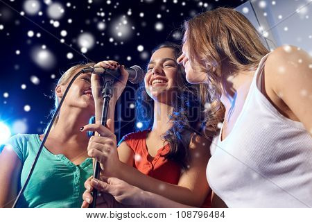 party, holidays, celebration, nightlife and people concept - happy young women singing karaoke in night club and snow effect