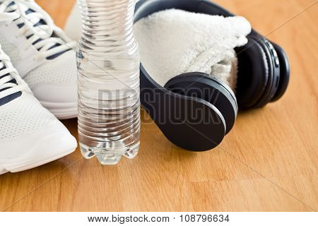 the sport concept. headphones, shoes and water in bottle