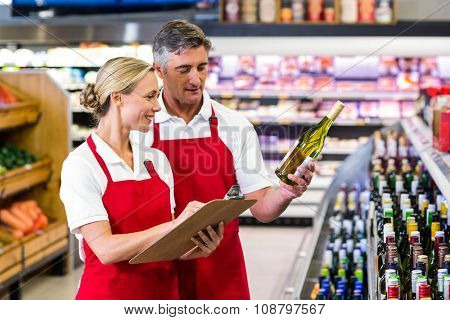Two colleagues holding bottle of wine and writing on clipboard at supermarket
