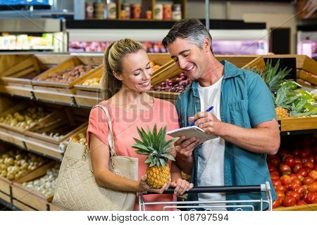 Smiling couple looking at the grocery list at the supermarket