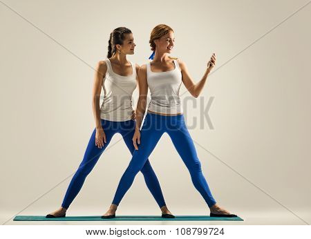 women with smartphone. yoga in pair