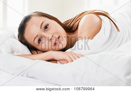 Portrait of the young woman in bed on pillow