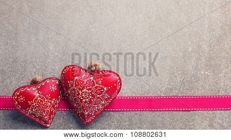 Two Decorative  Hearts  And Ribbon On  Grey Slate  Background.