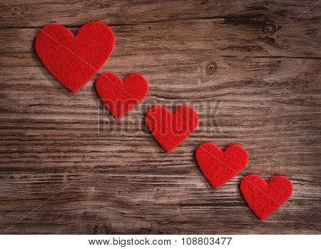 red hearts on a wooden surface