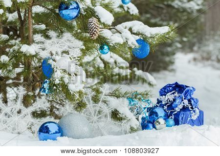 Evergreen snowy pine tree decorated with Christmas baubles and wrapped presents on ground