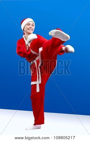 Beautiful girl dressed as Santa makes a karate kick left foot