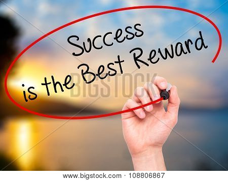 Man Hand writing Success is the Best Reward with black marker on visual screen.