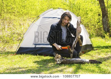 Man chopping wood to tent
