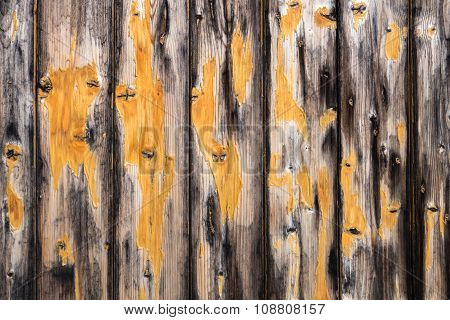 Board wall with remnants of yellow paint