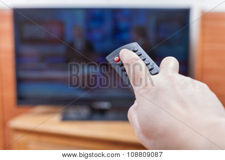Hand Turns On News On Tv By Remote Control