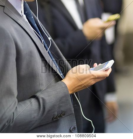 Businessmen using their cell phones on subway.