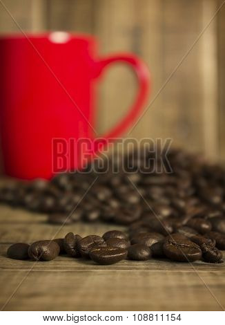 coffee beans and red cup on the wooden table