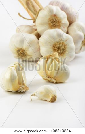 close up of garlic bulbs and cloves on white background