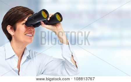 Business woman with binoculars over blue background.