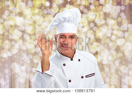 Handsome Chef man over abstract Christmas background.