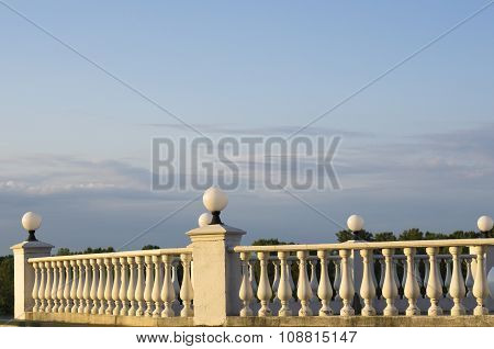 Decorative Fence Of Columns On Promenade On Background Of Blue Sky And Clouds