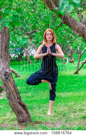 Woman In Black Clothes Doing Yoga In The Park