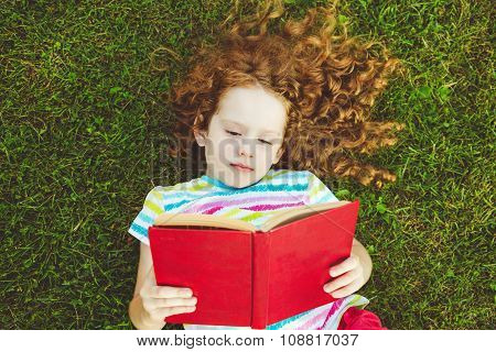 Little Girl With A Book Lying In The Grass.