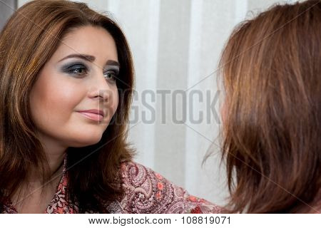 Middle-aged Woman Looking At Herself In The Mirror.