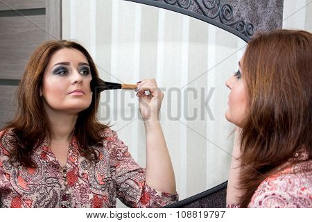 Woman Looking In The Mirror And Applies Himself Blush.