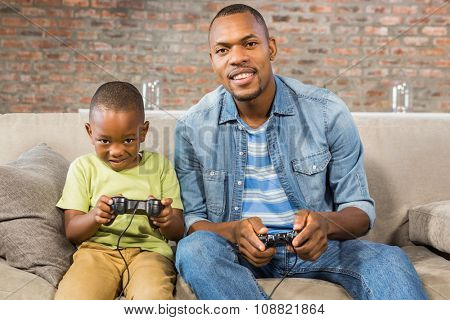 Father and son playing video games together in living room