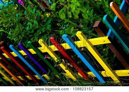Multi Colored Rainbow Wooden Fence In Garden Background