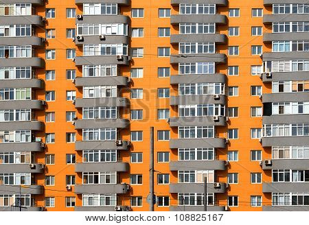 Orange And Grey Brick House With Many Windows And Balcony Background