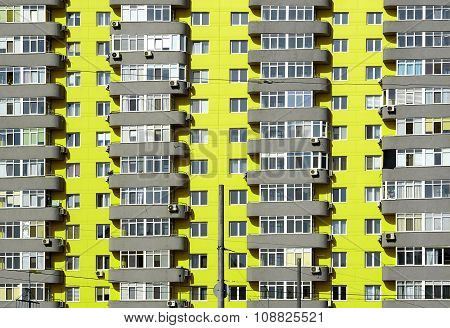 Acid Yellow And Grey Brick House With Many Windows And Balcony Background