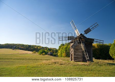 Windmill Standing In The Field Against The Blue Sky