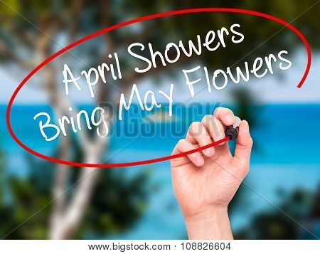 Man Hand writing April Showers Bring May Flowers with black marker on visual screen.