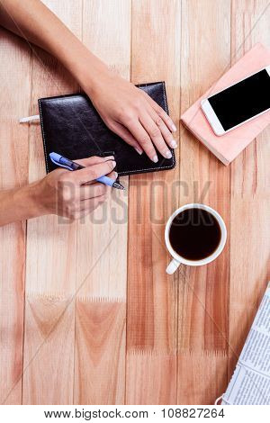 Overhead of feminine hands closing agenda with coffee and smartphone on table
