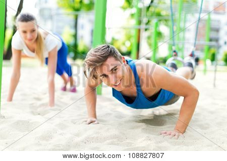 Couple exercising at outdoor gym