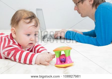 child playing while father is working on laptop